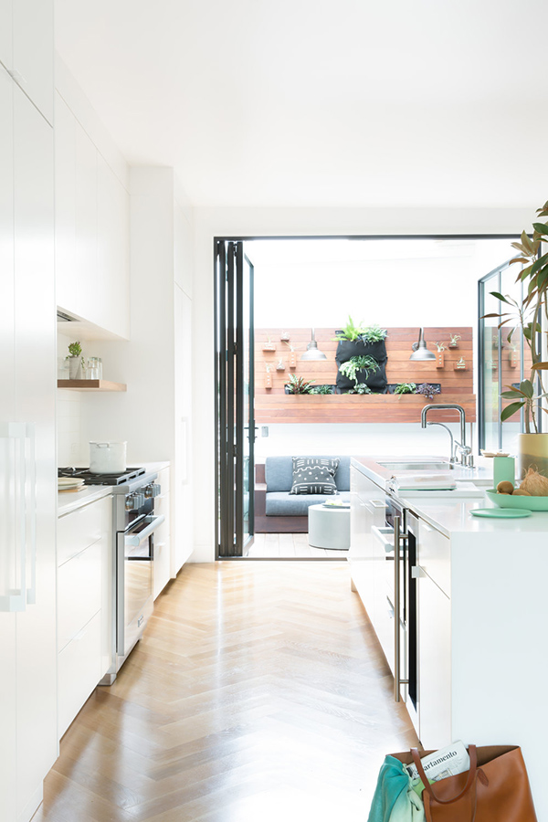 The kitchen features all-white decor and an entrance to the terrace