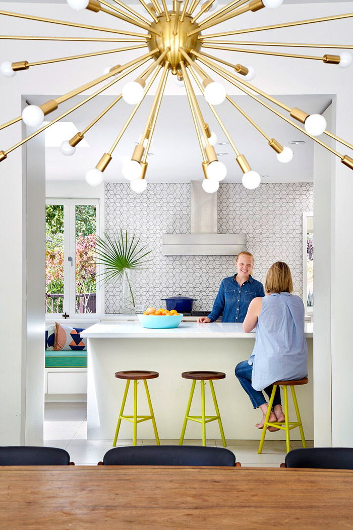 The kitchen features geometric tiles, colorful stools and is bright and open