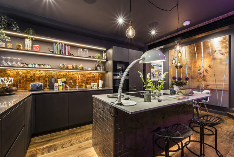 The kitchen is an artistic space with shiny gold tiles, a large tiled kitchen island and dark grey furniture