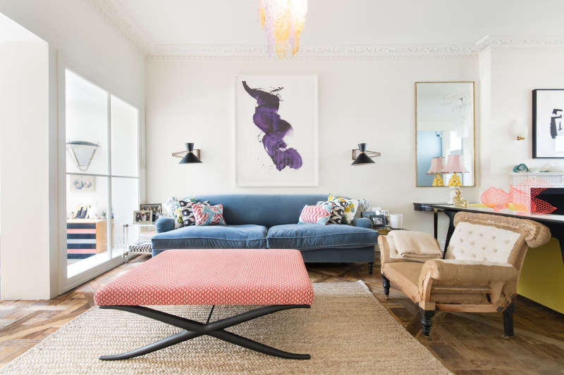 This is the second part of the living room, with a blue sofa and a cool upholstered coffee table or ottoman