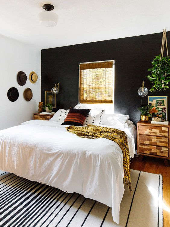 a boho and rustic space with a black headboard wall is balanced with warm-colored wood and a window in this wall