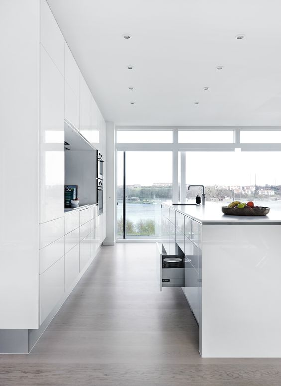 all-white minimalist kitchen with sleek cabinets and great views with a large kitchen island