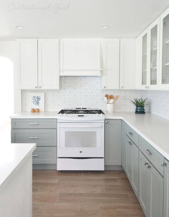 an ethereal kitchen with dove grey and white cabinets and a geometric tile backsplash looks very inviting