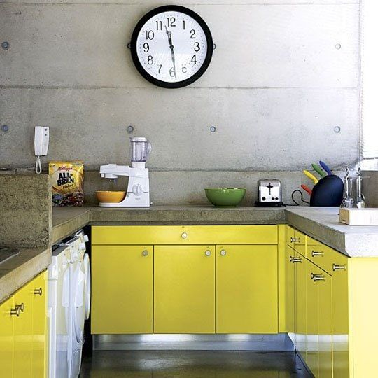 an industrial kitchen with lemon yellow cabinets, concrete walls and concrete countertops