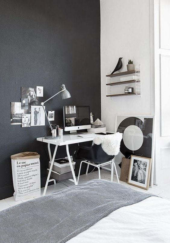 the home office nook is defined by a black wall and a matching chair to visually separate it