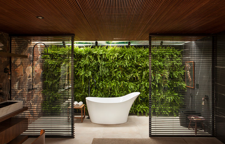 The bathroom also features a gorgeous living wall and wooden screens to divide the sink zone from the bathing one