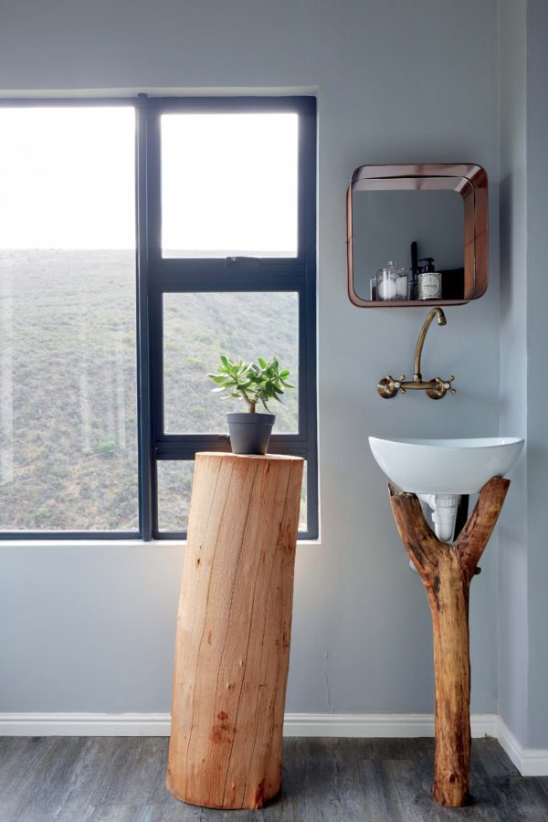 The bathroom features a tree stump stand and a branch sink holder, which remind you that it's an eco cabin