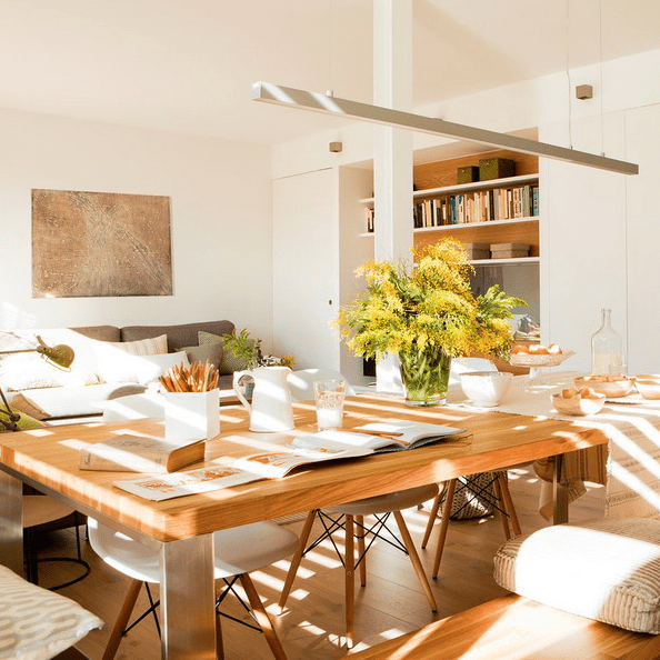 The dining area features a comfy table that can accomodate several people, modern chairs and a hanging lamp