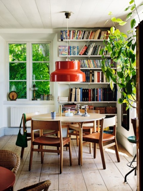 The dining space is done with a wwooden dining set and a round table, a number of bookshelves in the corner stores a lot of books