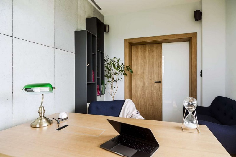 The home office was done with navy chairs, a wall bookcase, a light colored wooden desk