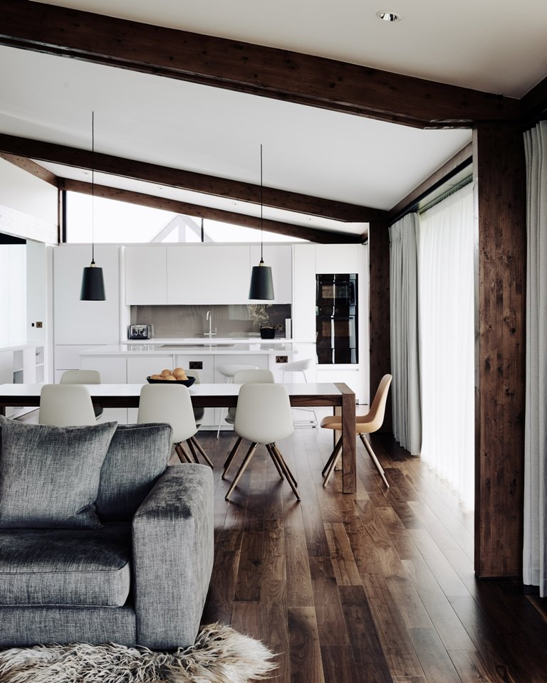 The kitchen is done in white, there are wooden beams and floors, and a dining set with a wooden table and white chairs
