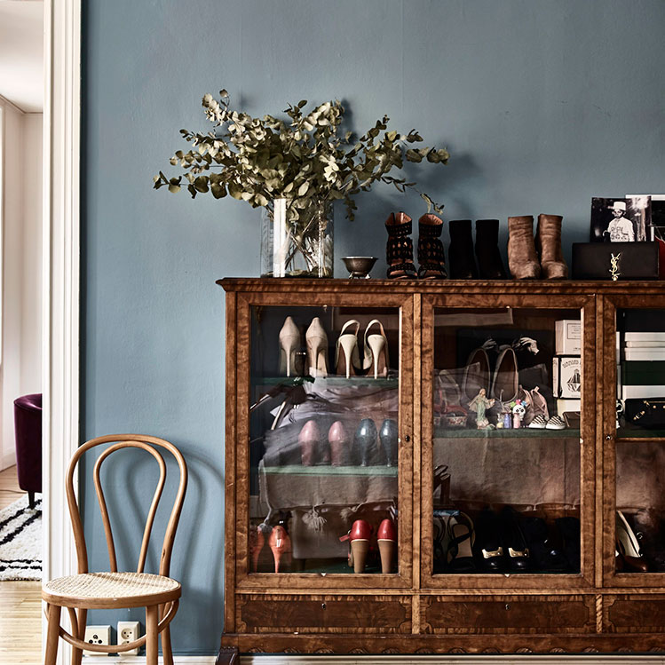 There's a vintage glass sideboard, which is used for storing shoes that the owner loves very much