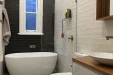 04 a black tile wall creates a bold contrast and makes the bathtub space stand out