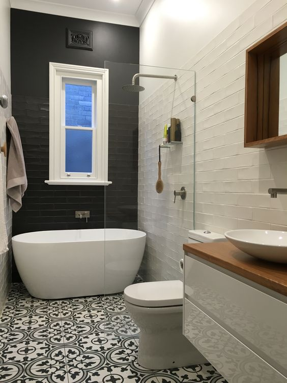 a black tile wall creates a bold contrast and makes the bathtub space stand out