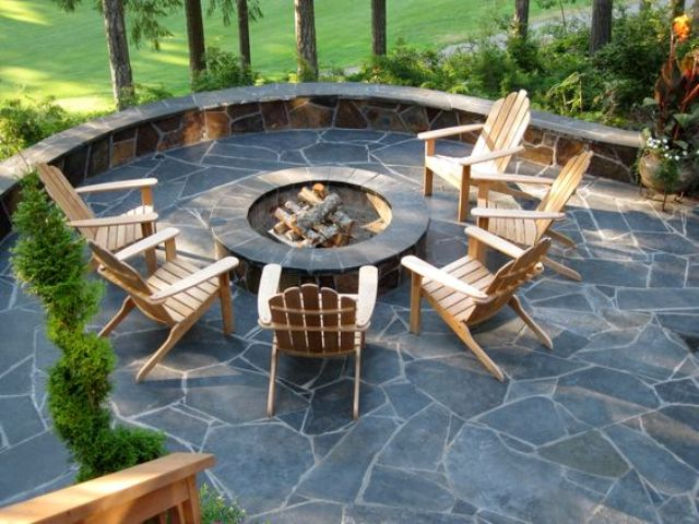 a stylish stone patio with a round firepit and simple wooden chairs to enjoy comfort