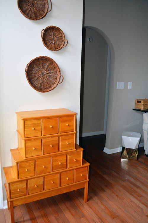 an antique apothecary cabinet in bold orange for accentuating an entryway