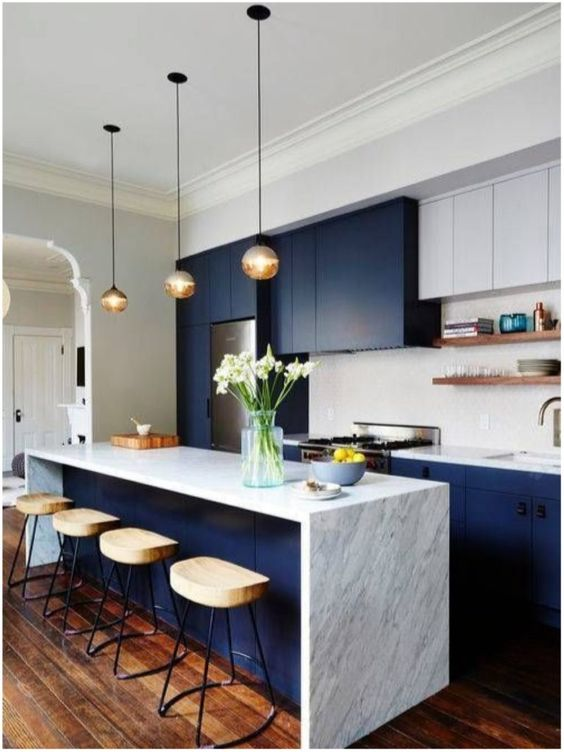 navy and white kitchen with marble countertops, bubble pendant lamps and comfy wooden stools