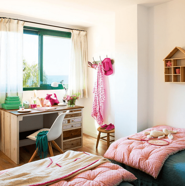 The kids' room is done with bold green and pink, there's a large window to bring light in, and two beds