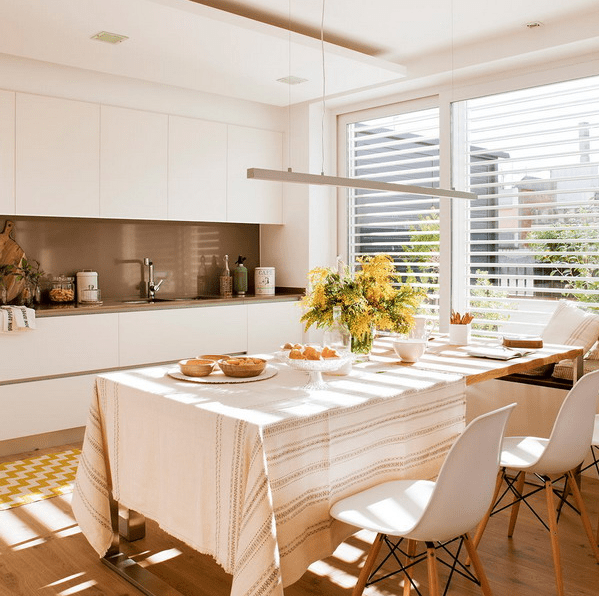 The kitchen features a sleek white kitchen with a brown backsplash, and a large window bring much light in