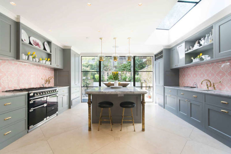 The kitchen is done in graphite grey, with pink patterned tile backsplashes and some brass touches