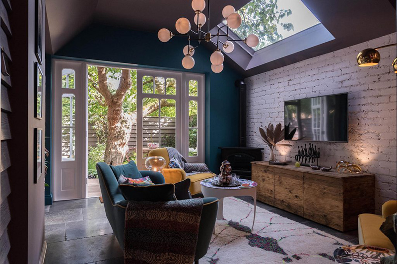 The living room features a teal wall and velvet sofa in the same color, some jewel toned chairs, skylights for additional natural light