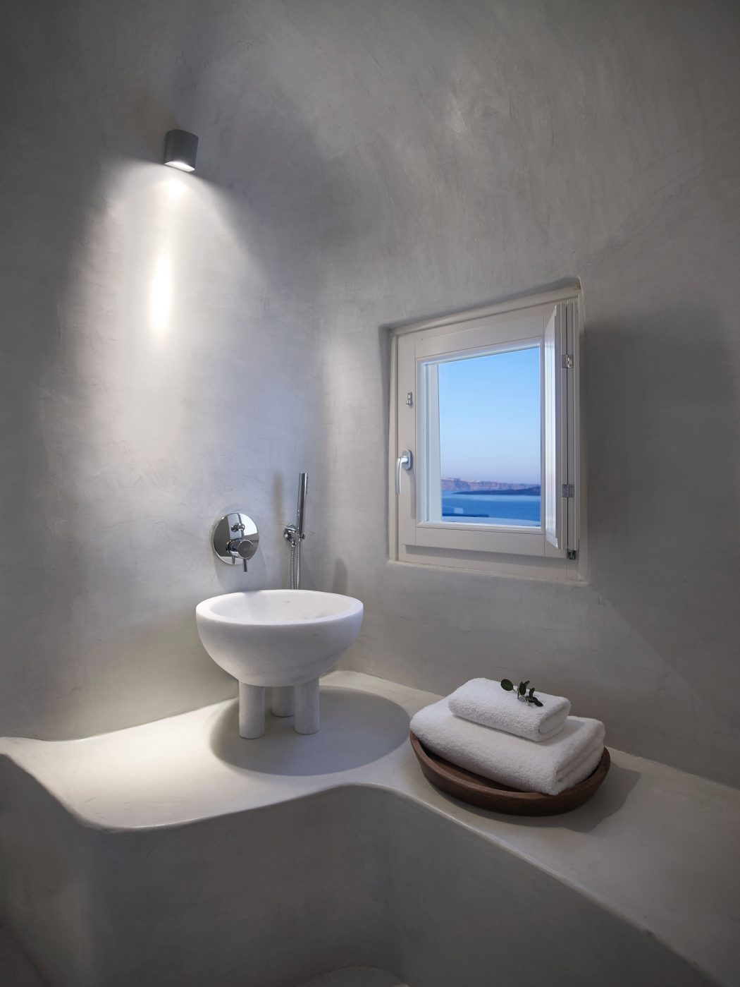 The master bathroom features a whumsy free standing sink on small legs and a small window with a view