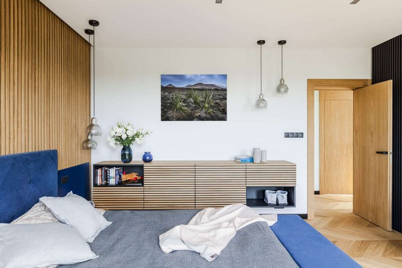 The master bedroom features a wooden slat wall and a floating sideboard and a blue upholstered bed