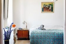 05 The master bedroom is done with mid-century modern furniture, colorful printed textiles, artworks and accessories