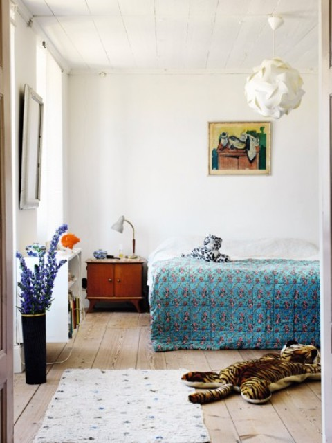 The master bedroom is done with mid century modern furniture, colorful printed textiles, artworks and accessories