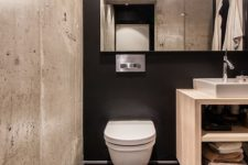 05 a black wall, black hex tiles and a contrasting concrete wall for a modern bathroom with an industrial feel