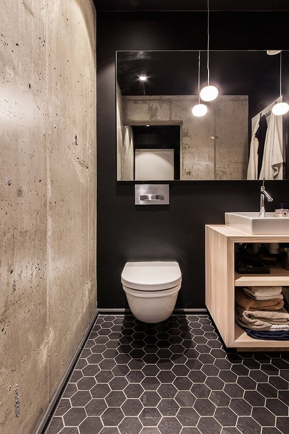 a black wall, black hex tiles and a contrasting concrete wall for a modern bathroom with an industrial feel