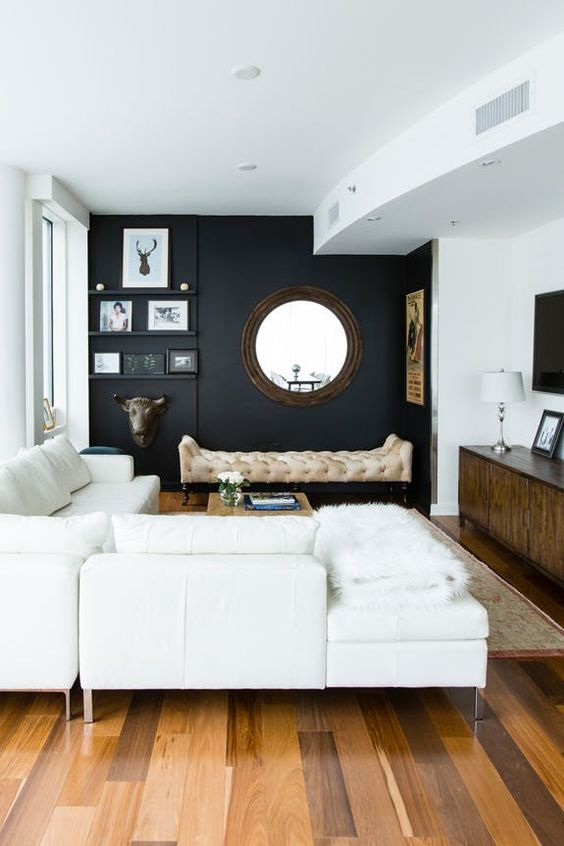 a chic modern space with a black wall, creamy furniture, walls and a ceiling and cool accessories and details