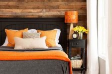 05 a cozy bedroom with a reclaimed wooden wall and bold orange accents that add a cheerful touch to the space