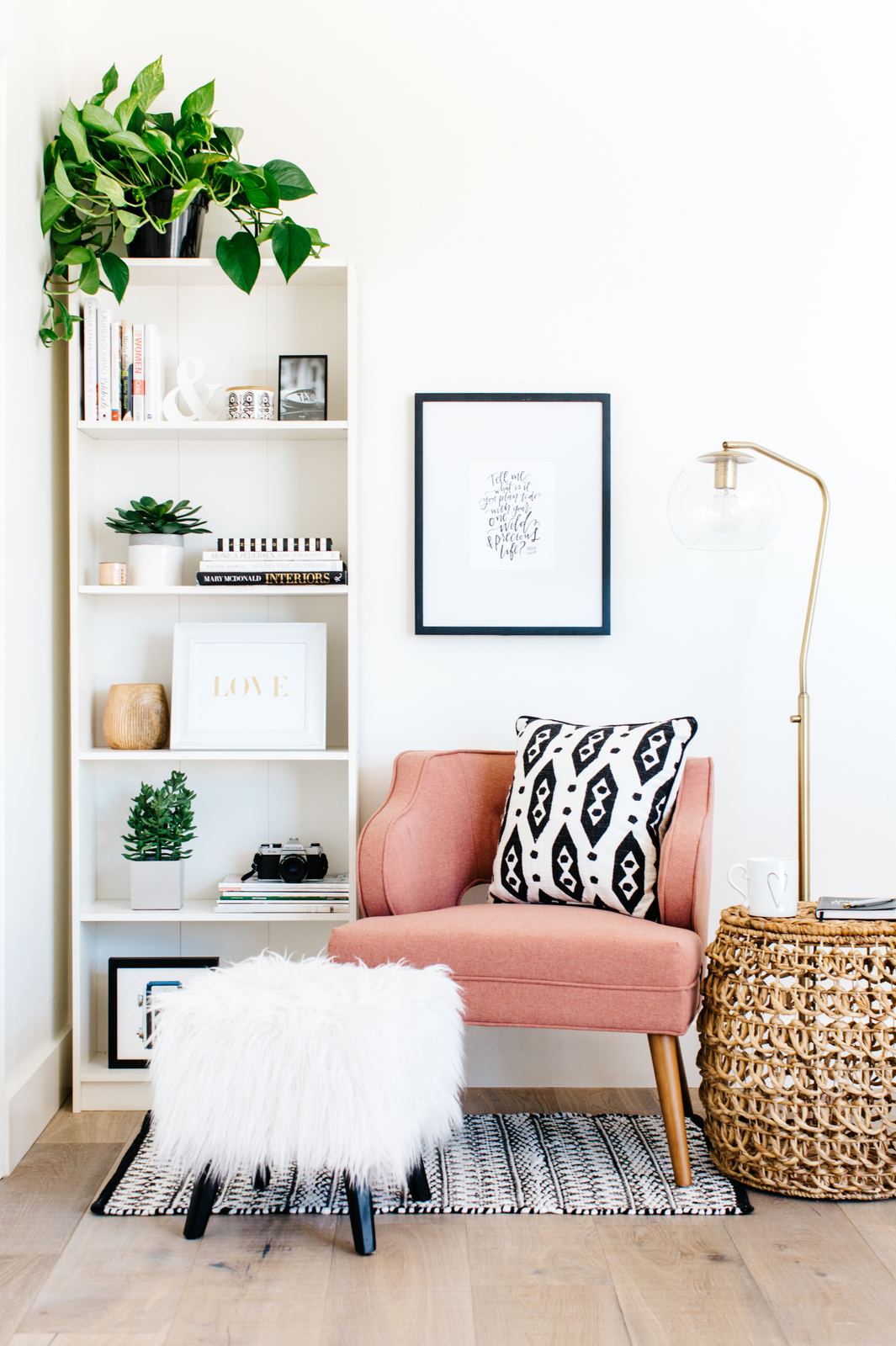 a cozy corner with a pink armchair, a floor lamp and some poufs is an ideal reading nook and is very inviting