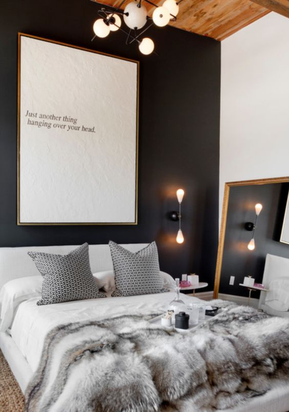 a luxurious bedroom with a black headboard wall, a large framed mirror and unique lighting fixtures