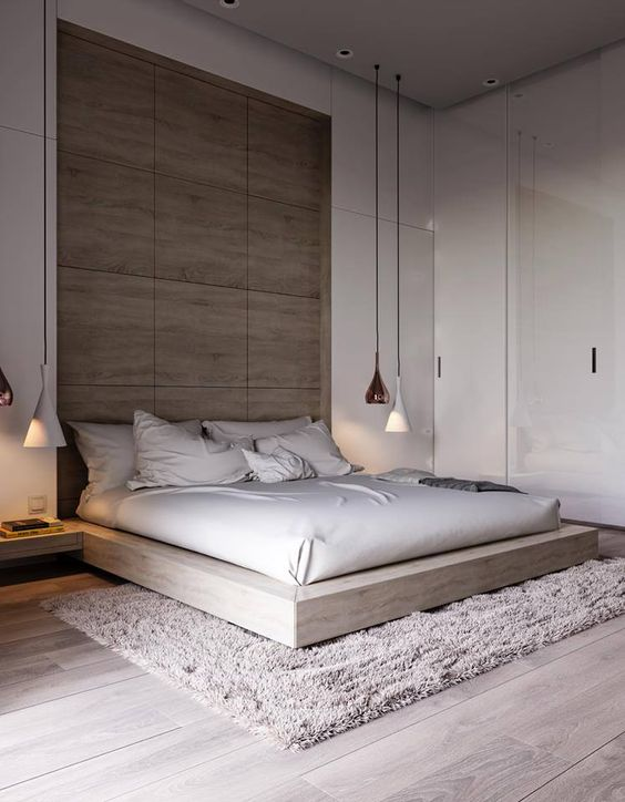 a modern space with glossy white walls, a wooden headboard wall, a wooden platform bed and white and copper hanging lamps