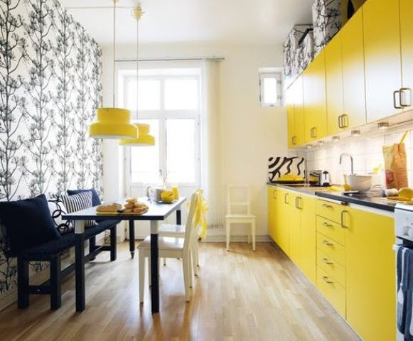 a small modern yellow kitchen with dark countertops, a dining zone accentuated with printed wallpaper