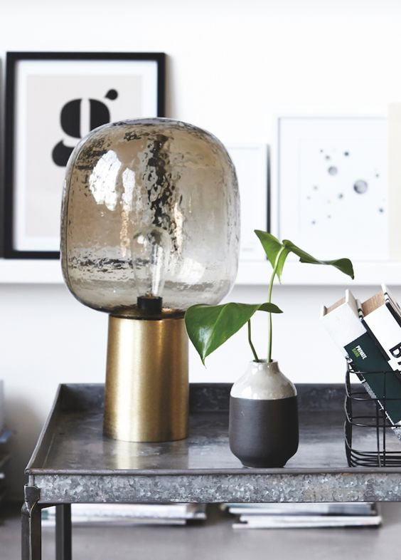 a smoked glass lamp with a brass base looks very chic and will give much light due to the clear glass