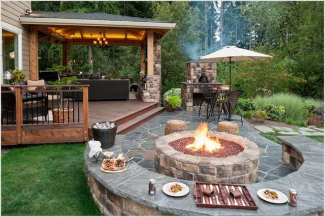 a stone part of the patio is decorated with a rounded bench and tabletop in one and a gorgeous firepit for cooking