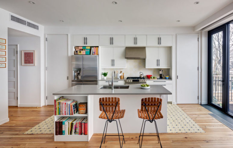 The kitchen is a neutral one, with metallic surfaces and lots of books, it's filled with natural light