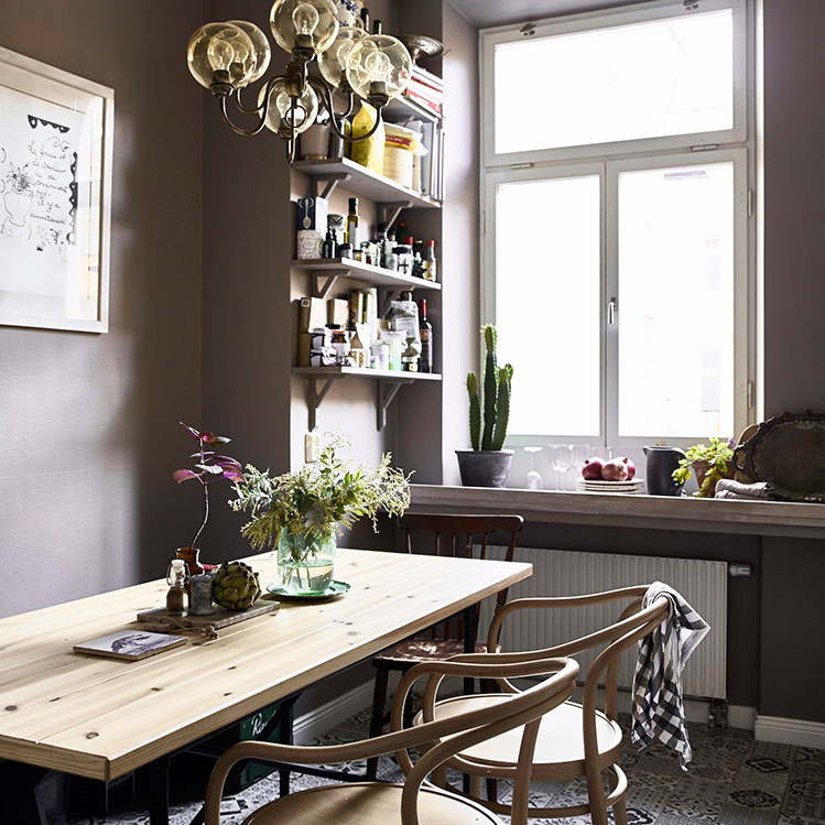The kitchen is painted grey but mosaic tiles on the floor make it stand out, and natural wood chairs and a dining table add a natural feel