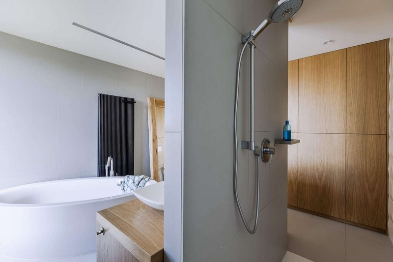 The master bathroom features a free standing bathtub, a shower and some wooden touches for coziness