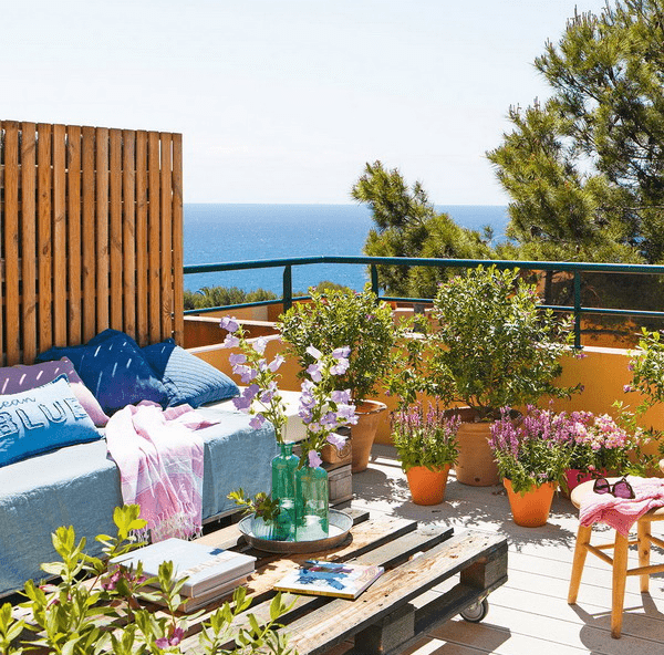 The terrace is decorated with some stools, a pallet table, a daybed and lots of potted flowers and greenery