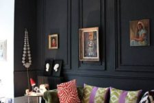 06 a black panel wall makes a statement in this space, with neutrals and muted colors, a green sofa and refined artworks