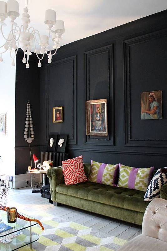 a black panel wall makes a statement in this space, with neutrals and muted colors, a green sofa and refined artworks
