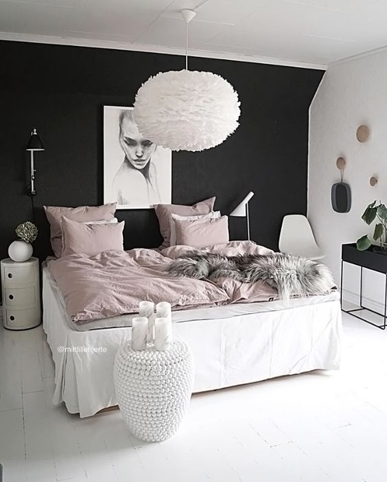 a girlish bedroom is calmed down with a black headboard wall, which stands out in this neutral space with blush touches
