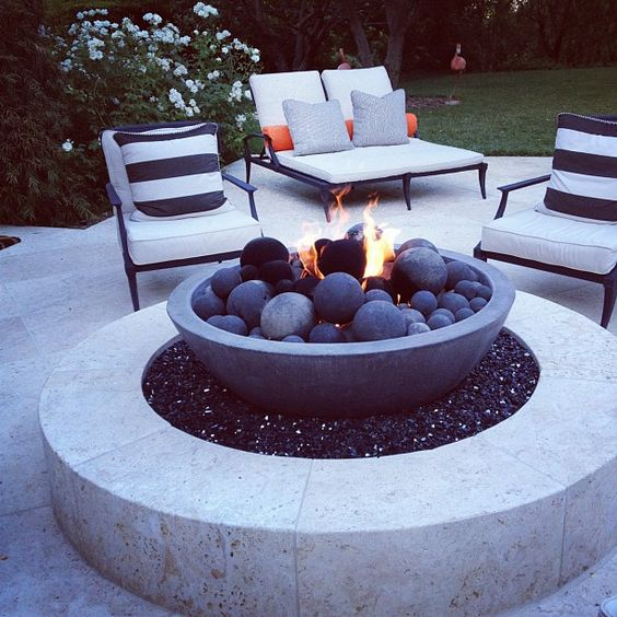 a modern bonfire space of white stone with an eye-catchy firepit with stone balls