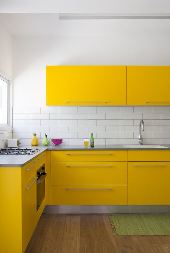 a modern yellow kitchen with stainless steel countertops and a white tile backsplash looks very eye-catchy