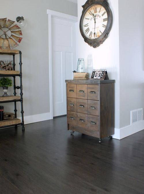 a small reclaimed wood apothecary cabinet placed on casters as a cute and eye-catchy entryway console