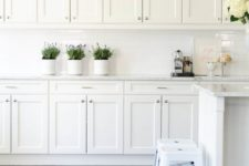 06 a vintage white kitchen with a white tile backsplash, stools and much storage space